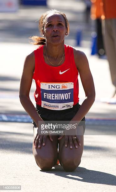 Firehiwot Dado of Ethiopia kneels on the ground after crossing the finish line to win the ING New York City Marathon November 6 2011 in New York Dado...