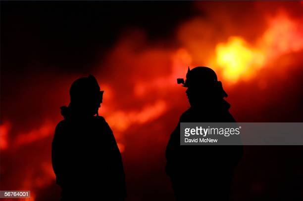 Fireifghters keep watch in the night over flames along State Route 241 toll road during an offseason wildfire in the Cleveland National Forest driven...