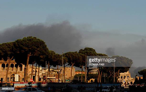 A fireman and a police officer watch a huge blaze breaking in via dell'Almone south of Rome at a warehouse containing around 1000 cars on July 12...