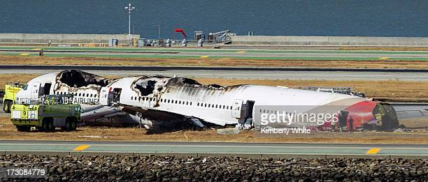 A fireman and investigator examine the tail wreckage from a Boeing 777 airplane that crashed while landing at San Francisco International Airport...