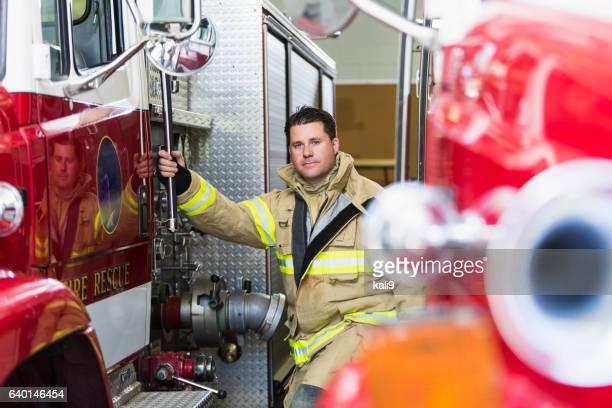 Fireman am Bahnhof bereit zum Klettern auf Feuerwehrauto