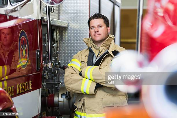 fireman at station standing next to fire truck - firefighter stock pictures, royalty-free photos & images