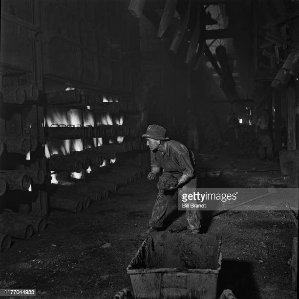 A fireman at the zinc smelting plant at Swansea Vale keeps the furnaces fed and firing at Llansamlet near Swansea South Wales 1943 Original...