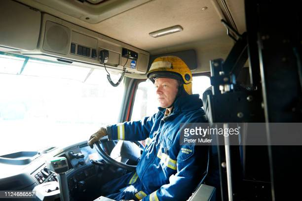fireman at wheel of fire engine - firefighter stock pictures, royalty-free photos & images