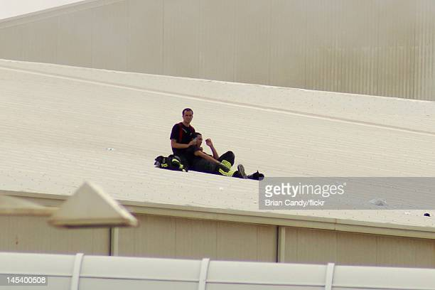 A fireman attends to an injured colleague on the roof of the Villaggio mall on May 28 2012 in Doha Qatar A fire started at the Villaggio mall...