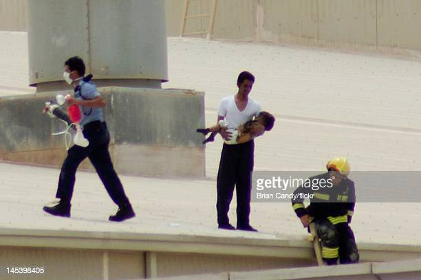 A fireman carries a child from the roof as emergency services seek to rescue people trapped in a fire at the Villaggio mall on May 28 2012 in Doha...