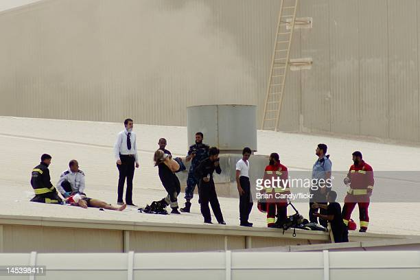 Fireman carries a child from the roof as emergency services seek to rescue people trapped in a fire at the Villaggio mall on May 28, 2012 in Doha,...