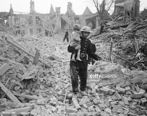 Fireman carries a young boy out of the rubble after a bombing raid, London, Circa 1940.