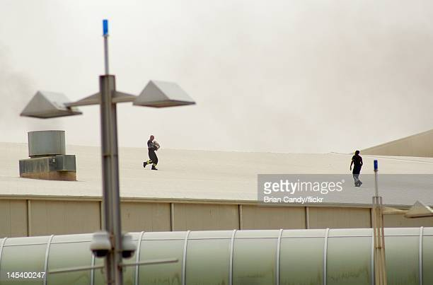 A fireman carries an injured child across a roof as emergency sevices seek to rescue people from a fire at the Villaggio mall on May 28 2012 in Doha...