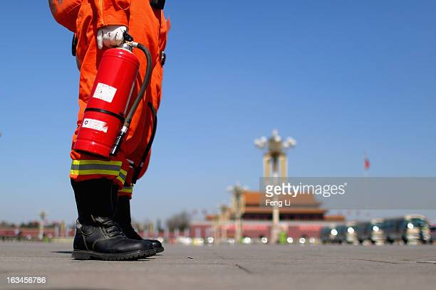 Fireman carrying a fire extinguisher stands on the Tiananmen Square during a plenary session of the National People's Congress on March 10, 2013 in...