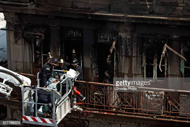 fireman carrying dead body after fire in johri mansion at kalbadevi, bombay mumbai, maharashtra, india - burned body stock pictures, royalty-free photos & images