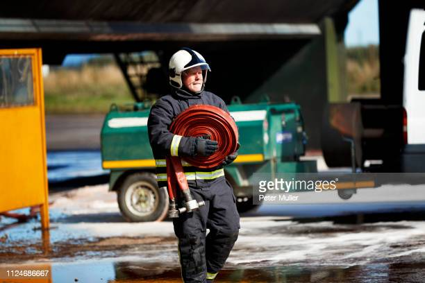 fireman carrying fire hose reel, darlington, uk - firefighter stock pictures, royalty-free photos & images