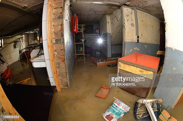 A fireman checks a flooded basement of a house on June 4 2013 in Rosenheim southern Germany AFP PHOTO / PETER KNEFFEL /GERMANY OUT