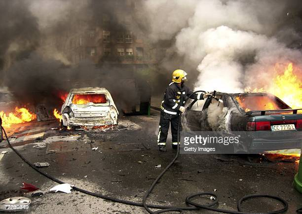 Fireman extinguishes flames at the scene where a car bomb exploded, injuring a bodyguard of a local council member from Spain's ruling Socialist...