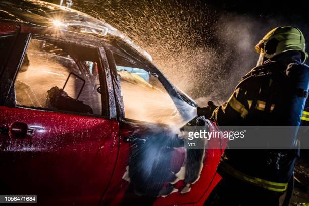 pompier d'extinction d'une voiture en feu - accident de la route photos et images de collection