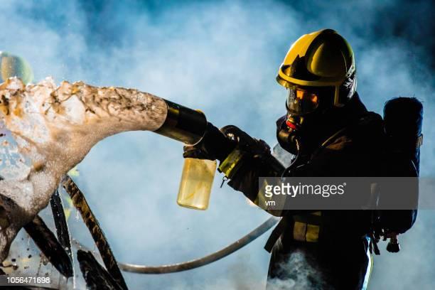 bombeiro, um carro em chamas com espuma de extinção - espuma sintética - fotografias e filmes do acervo