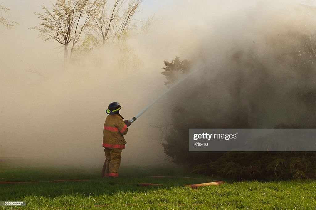 Fireman Fighting House Fire : Stock Photo