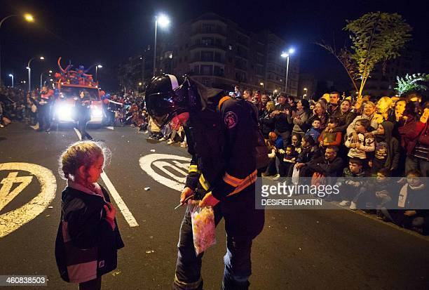 A fireman gives sweets to a young girl during the Three Wise Men Parade in Tenerife on the Spanish Canary island of Tenerife on January 5 on the eve...