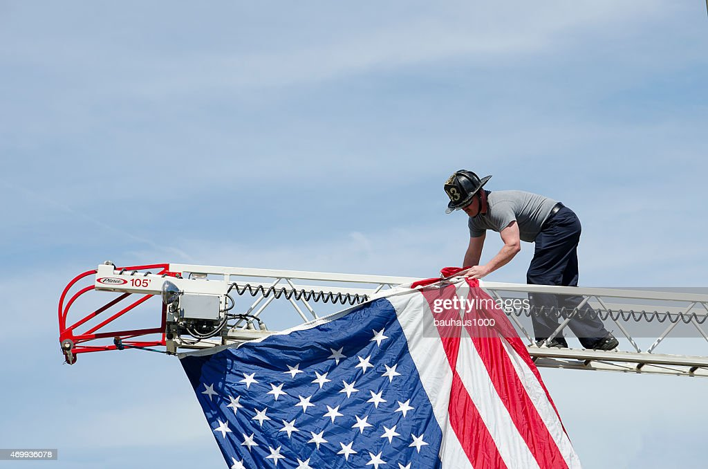 Fireman hanging a flag in a Patriotic Parade : Stock Photo
