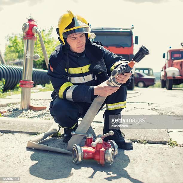 Fireman in Aktion mit einem Feuerwehrschlauch