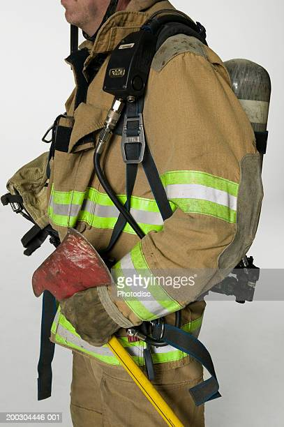 Fireman in full uniform holding axe in studio, mid section
