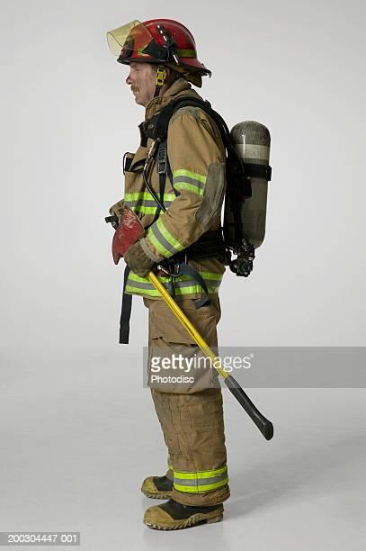 Fireman in full uniform holding axe in studio, proflie