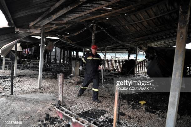 A fireman is at work at the burnt facilities of the school for refugee children part of the One Happy Family NGO's project on the island of Lesbos on...