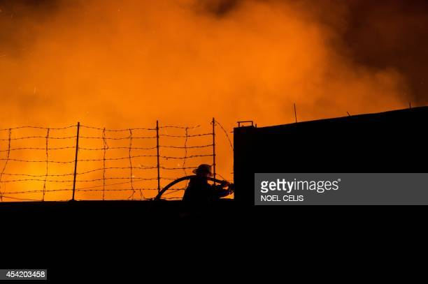 A fireman is silhouetted as he fights a fire that engulfed a warehouse in Manila on August 26 2014 AFP PHOTO/NOEL CELIS