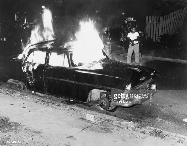 Fireman looking startled as snipers fire on him and his colleagues as they approach a burning car in Detroit, Michigan, July 1967. Violence erupted...