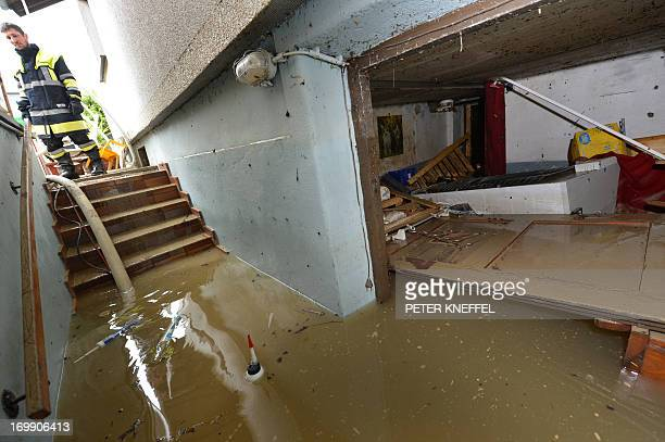 A fireman looks at a flooded basement of a house on June 4 2013 in Rosenheim southern Germany AFP PHOTO / PETER KNEFFEL /GERMANY OUT