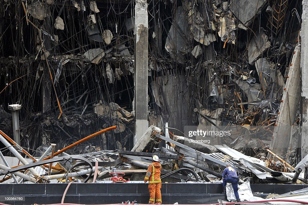 A fireman looks at the partially collapsed remains of Central World, the nation's largest shopping center, in Bangkok, Thailand, on Monday, May 24, 2010. Efforts to clean up the city's commercial district gathered pace after the area was torched by rioting anti-government protesters. Photographer: Udo Weitz/Bloomberg via Getty Images