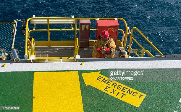 A fireman mans a water cannon during a helicopter landing operation at one side of the helideck of La Muralla IV exploration oil rig operated by...