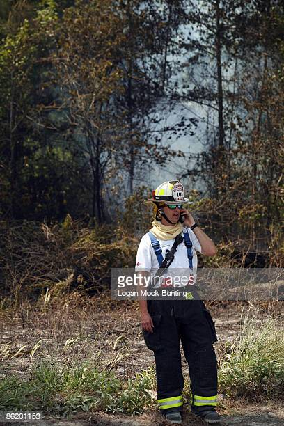 A fireman monitors backfires lit by the Forestry Service meant to contain wildfires April 24 2009 in Horry County North Carolina The backfires are...