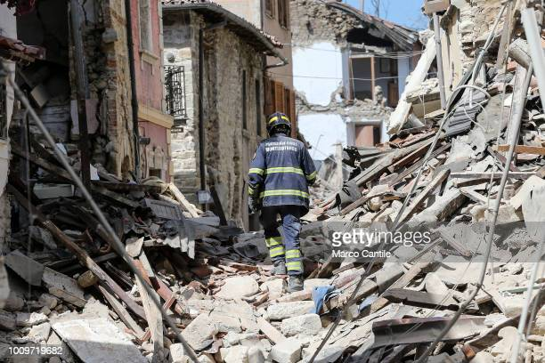 A fireman on the rubble of a two houses completely collapsed after the earthquake that hit the city of Amatrice in central Italy