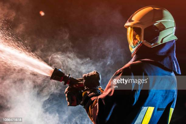 fireman operating a water fire hose - firefighter stock pictures, royalty-free photos & images