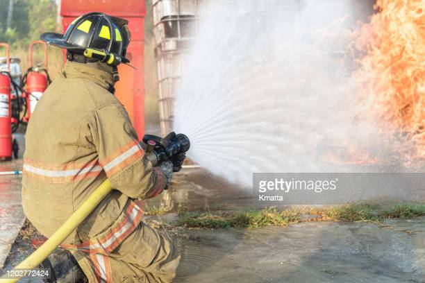 fireman operating a water fire hose. - in flames i the mask stock pictures, royalty-free photos & images
