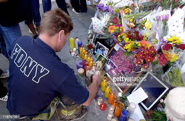 Fireman Patrick Parrott lights a candle at a memorial for victims from a Manhattan Fire House 13 September 2001 in New York Fourteen firefighters...