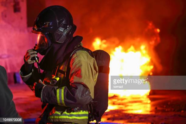 fireman preparing his gas mask before going into fire - fire protection suit stock photos and pictures