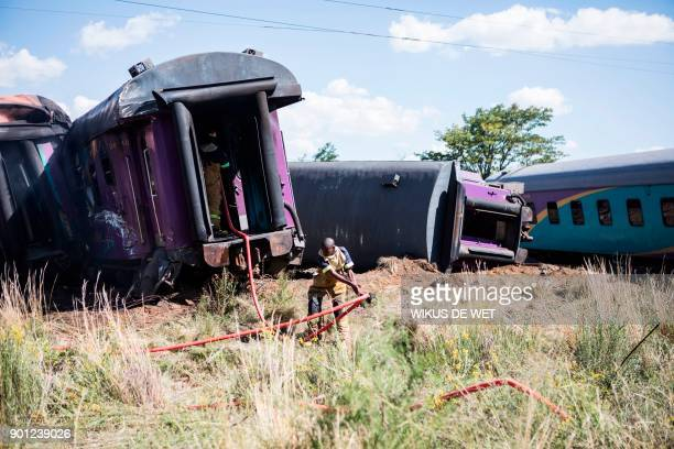 A fireman pulls a hose as he works beside derailed train carriages after an accident near Kroonstad in the Free State Province some 110kms southwest...