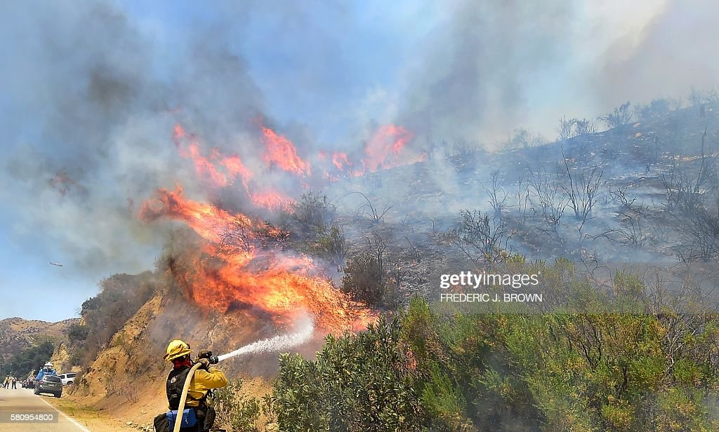 A fireman puts out a fire off Placerita Canyon Road in Santa