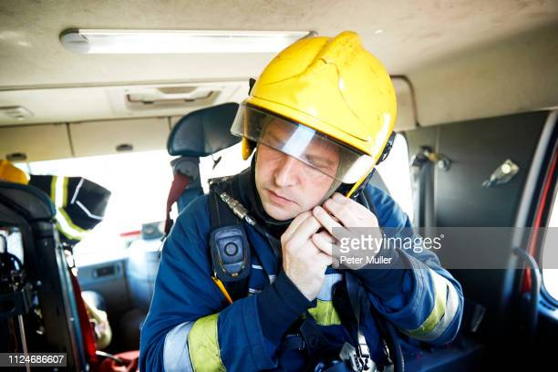 fireman putting on helmet in fire engine - firefighter stock pictures, royalty-free photos & images