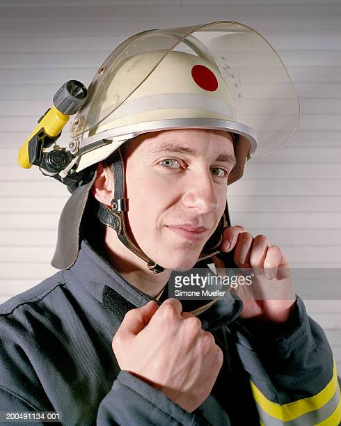 Fireman putting on helmet, portrait