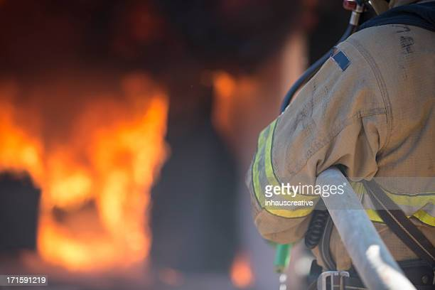fireman putting out a bedroom fire - fire station stock photos and pictures