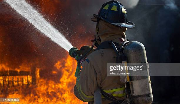 fireman putting out a bedroom fire - firefighter stock pictures, royalty-free photos & images