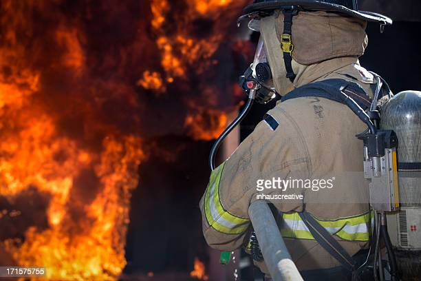 fireman putting out a house fire - disaster relief stock photos and pictures