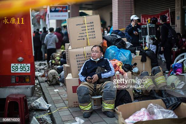 TOPSHOT A fireman rests near a collapsed building in the southern Taiwanese city of Tainan on February 7 following a strong 64magnitude earthquake...