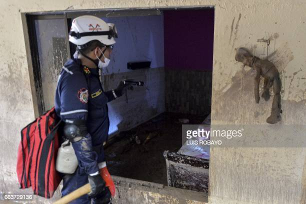 A fireman searches for victims inside a muddy house following mudslides caused by heavy rains in Mocoa Putumayo department southern Colombia on April...