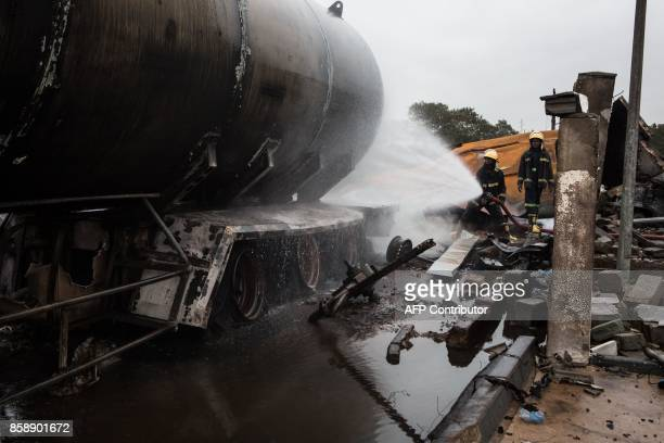 A fireman sprays water on a tanker the site of an explosion in Accra on October 8 2017 a day after a gas tanker caught fire triggering explosions at...