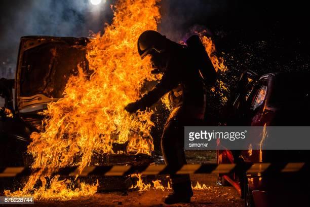 bombeiro em pé perto de fogo - fire protection suit - fotografias e filmes do acervo