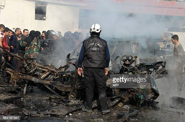 A fireman stands infront of a burnt out vehicle as Syiran civilians look on at the site of a barrel bomb attack reportedly dropped by government...